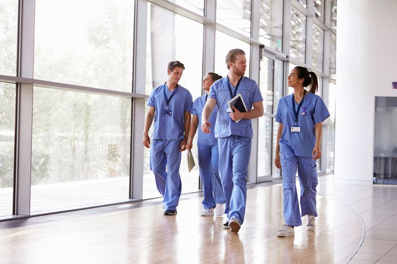 A group of JCU Master of Nursing Graduates walk down a hospital hallway talking.