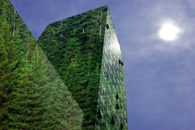 An office building shows reflections of green trees against the sky.