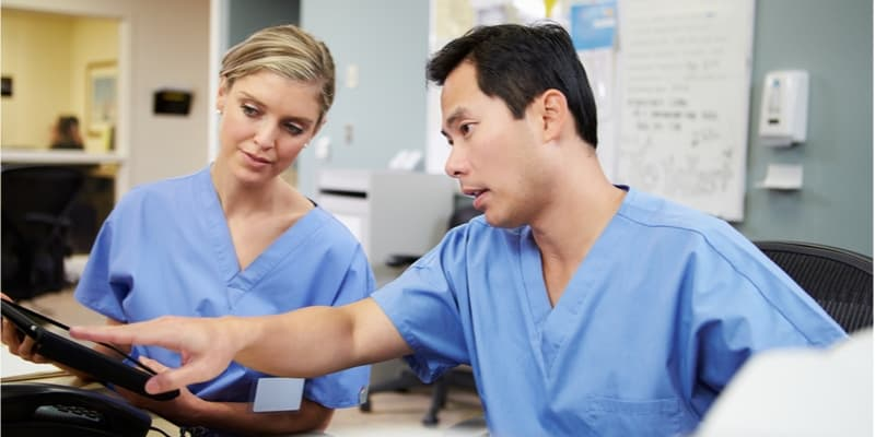 Male and female nurse wokring together using a tablet