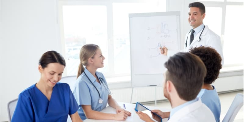 Group of happy nurses with mentor meeting and drawing on flip board at hospital
