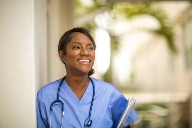 A smiling nurse wearing scrubs and a stethoscope.