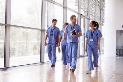 A group of JCU Master of Nursing Graduates walk down a hospital hallway talking.