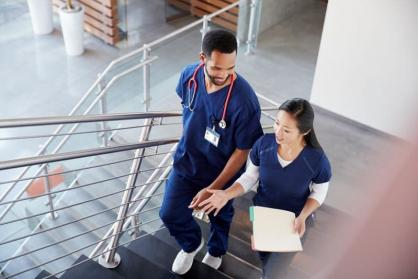 Two nurses walk up a flight of stairs in a hospital, talking and smiling.