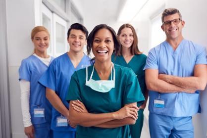 A team of smiling nurses stands together.