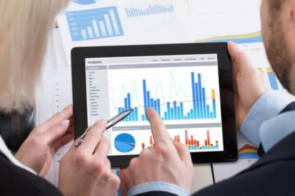 A businessman and businesswoman interpreting data on their tablet.