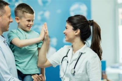 Female nurse high fiving her young patient